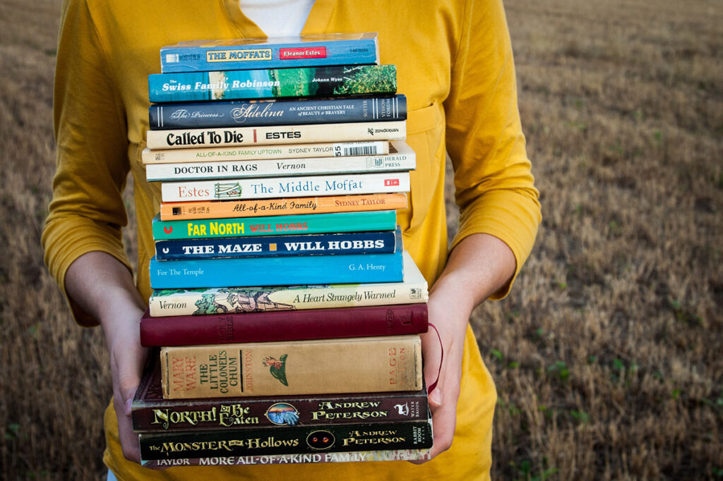 A woman holds a large stack of hardcover books to show how spines can change while self-publishing with IngramSpark
