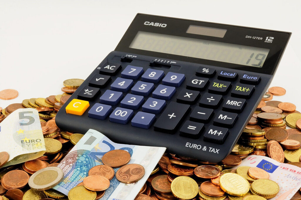 Calculator with coins and bills gathered around it to show the rising costs of self-publishing with IngramSpark