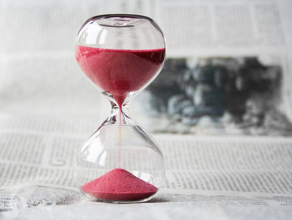An hourglass is about three quarters full on top with the other quarter of sand on the bottom to show the slow passage of time while self-publishing with IngramSpark
