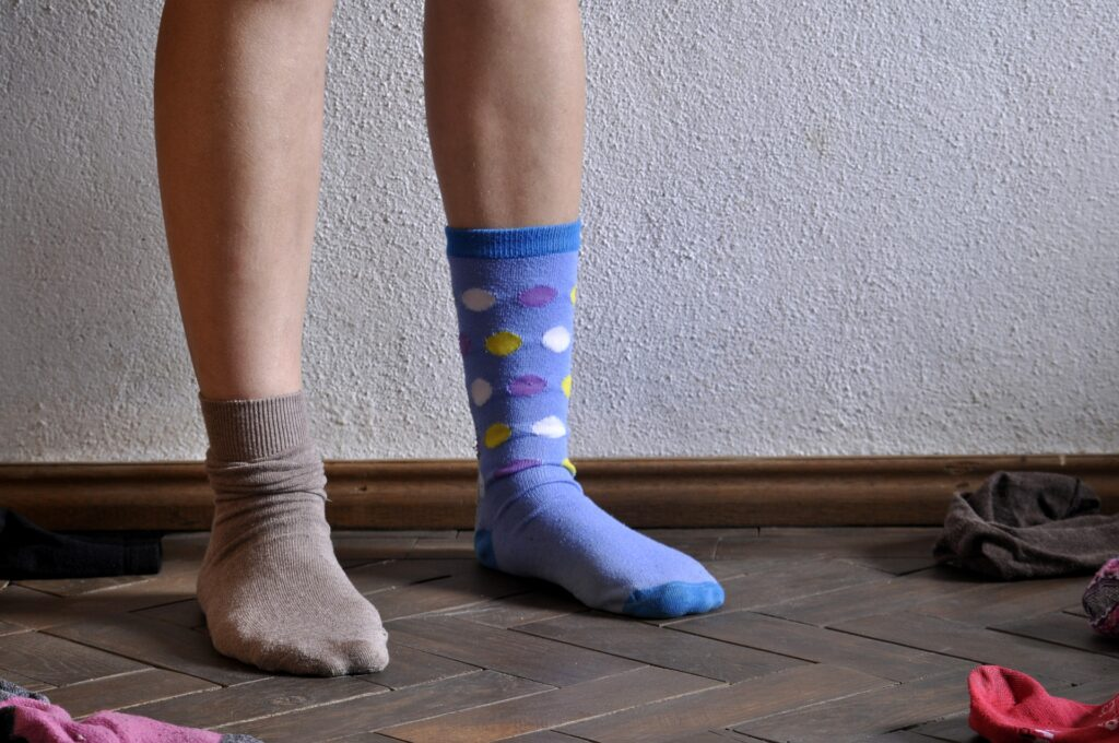 Getting dressed as way to cope in quarantine while working from home: Image of feet, one with an ankle-length brown sock and the other with a mid-calf-length purple sock with multi-colored spots.