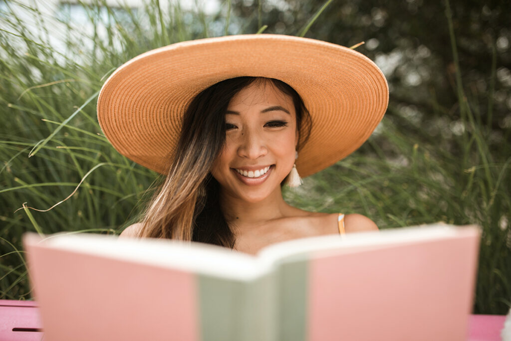 Woman in a sun hat while reading a book and smiling
