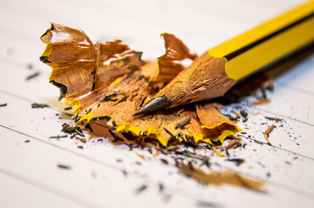 A pencil has been sharpened and is lying on its shavings