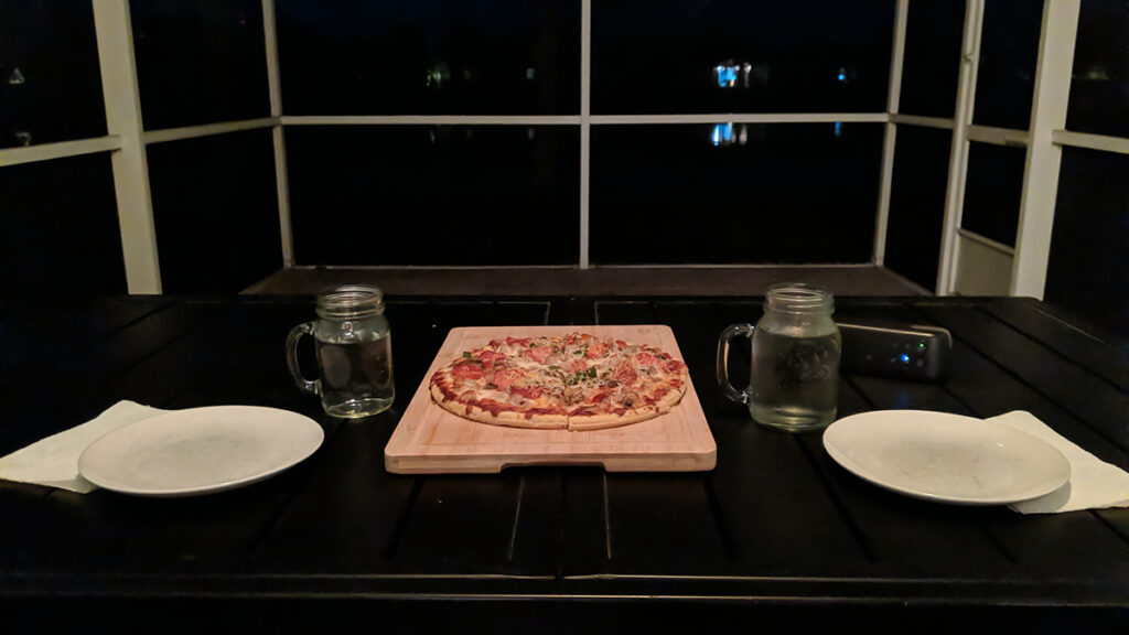 Pizza on a cutting board displayed on a patio table in the author's screened lanai