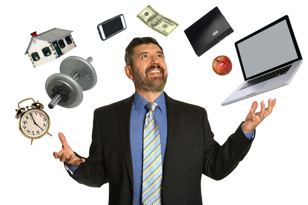 A man in a suit smiles while juggling a laptop, alarm clock, dumbbell, house, money, cell phone, binder, and an apple.