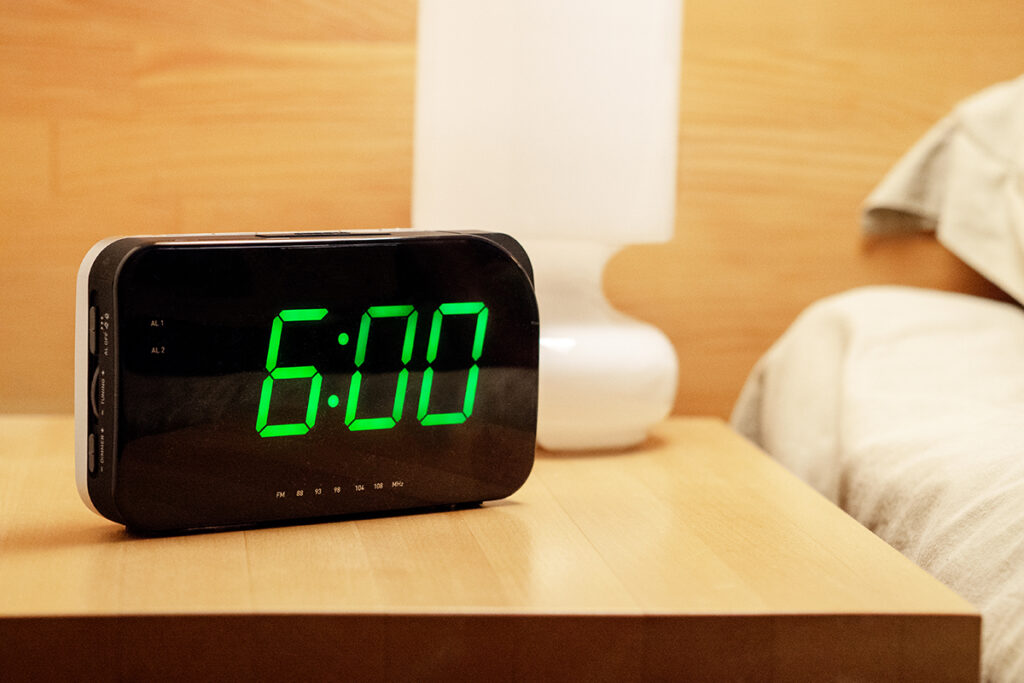An alarm clock displaying 6:00 is placed on a nighstand next to a bed.