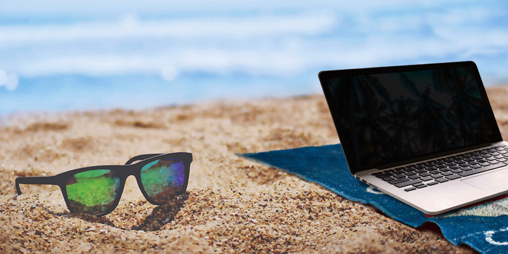 A laptop and sunglasses on a beach as one of the reasons to become a freelancer