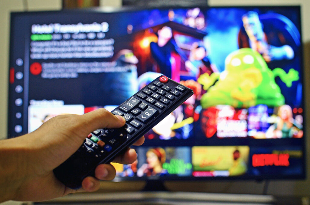A hand holds a remote control in front a large-screen TV showing a streaming menu