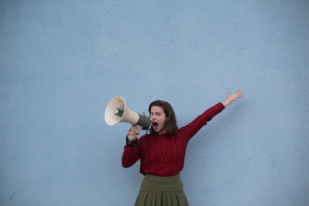A woman attempts to speak up using a megaphone