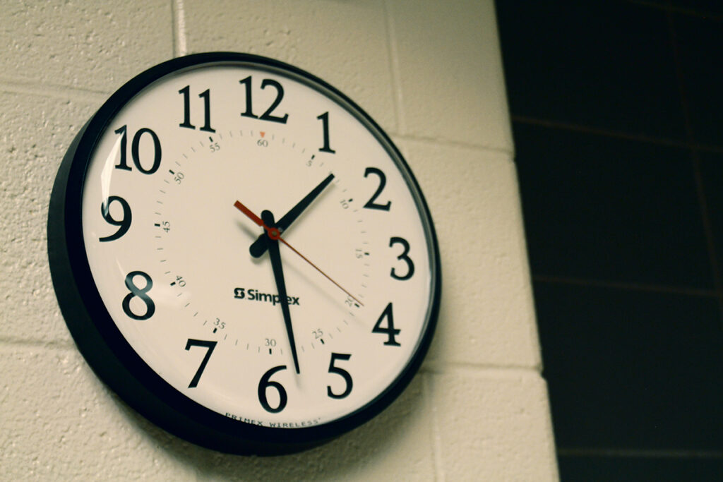 An analog clock on a concrete wall